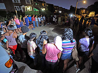 Dozens of neighbors and family members gathered at the scene where 13- and 17-year-old brothers were fatally shot inside a home in the 1300 block of Westbury Drive in Philly´s Overbrook Park section. (Photo / Tom Kelly IV)