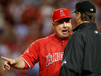 The Los Angeles Angels manager Mike Scioscia, left, talks with third<br />base umpire Tim McClelland about a fifth inning double tag by Angels<br />catcher Mike Napoli against New York Yankees Robinson Cano and Jorge Posada at Game 4 of the ALCS.