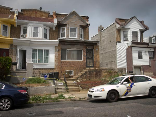 Philadelphia 35th District patrol car sits in front of 4846 N. 9th St. ( white row house) at left after children were allegedly removed after police found the home to be unsanitary. Photograph from Thursday morning August 8, 2013. ( ALEJANDRO A. ALVAREZ / STAFF PHOTOGRAPHER )