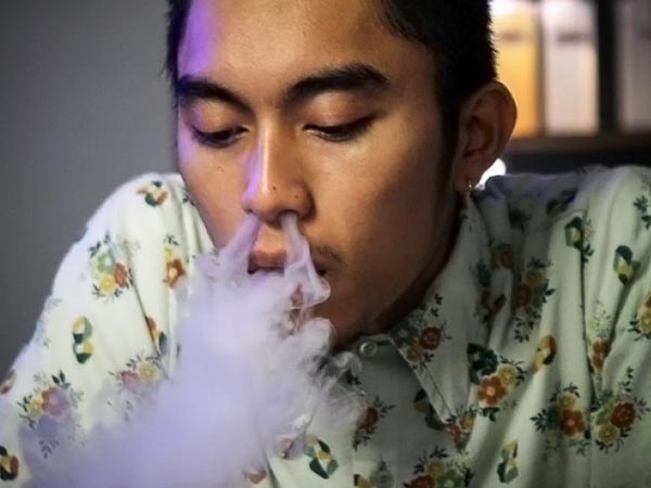 """""""Duck"""" exhales after vaporizing behind the counter at Exclusive Vape Shop in Philadelphia on Thursday, Dec. 12, 2013. (Stephanie Aaronson/Philly.com)"""