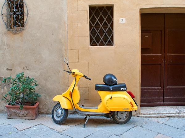 Pienza, Italy: Yellow Piaggio Vespa scooter parking in a street of the ancient village of Pienza, Tuscany.