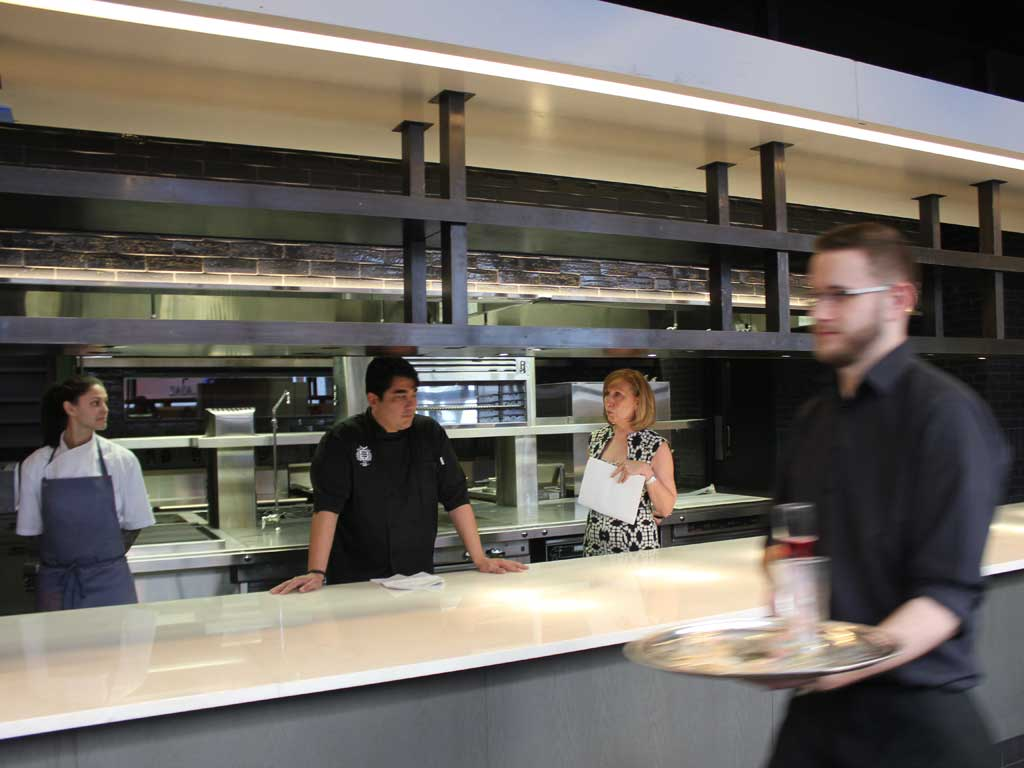 Behind the kitchen counter at Volver in the Kimmel Center are (from left) chef de cuisine Natalie Maronski, chef Jose Garces, and designer Marguerite Rodgers.