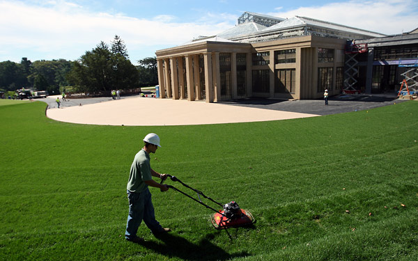"""Once flat, now sloping: Mike Zawislak, a Longwood Gardens grounds crew member, uses a """"hover"""" lawnmower to cut the new sod on the newly terraced lawn facing the East Conservatory."""