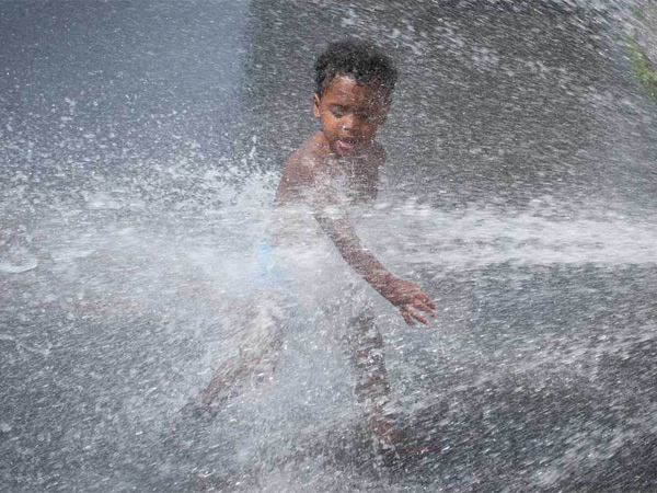 Two-year-old Camren Amtos plays in a fire hydrant along 4th Street in Feltonville with his stepfather (not pictured) on July 2, 2014. (RON TARVER / Staff Photographer)