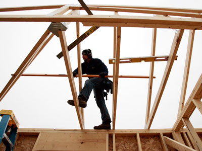 In this Nov.3, 2011 photo, Jim Weiler, of Jim Weiler Construction, sets a roof truss on a home under construction in LaPorte, Ind. Rising interest from would-be buyers is leaving U.S. homebuilders less pessimistic about the housing market. But tighter lending standards are still keeping many potential buyers from purchasing new homes. (AP Photo/Michigan City News Dispatch, Bob Wellinski)