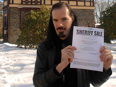 "Patrick Rodgers at his Wynnefield Heights home with the ""sheriff sale"" declaration against the mortgage company. (Tom Gralish / Staff Photographer)"