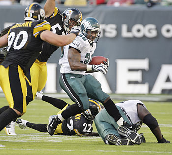 Brian Westbrook tries to leap over teammate Tra Thomas in the second quarter of the Steelers game. He injured his ankle on the play. (Ron Cortes / Inquirer).