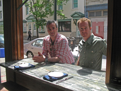 Pouget (left) and Rodgers sit on the sidewalk side of a window seat at Noble.