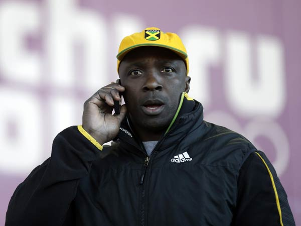 Winston Watts, the driver for JAM-1 of Jamaica, speaks on the phone after arriving at the sliding center during a training session for the men´s two-man bobsled at the 2014 Winter Olympics, Wednesday, Feb. 5, 2014, in Krasnaya Polyana, Russia. Watts and his team were unable to practice because the Jamaican team equipment and luggage did not arrive in Sochi. (AP Photo/Natacha Pisarenko)