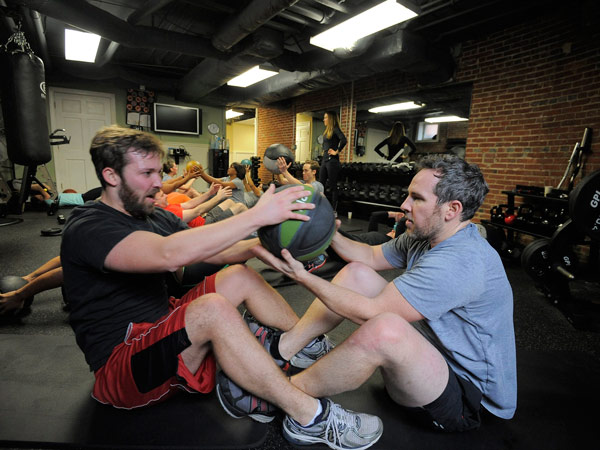 Left to right, Woody Heffern, marketing, and Jared Kelly, director of marketing, Agora Inc. pass a medicine ball while doing sit ups. They join other employees to enjoy a midday workout at the company gym. It´s one of many opportunities for workers to exercise several times per week. (Kim Hairston/Baltimore Sun/MCT)