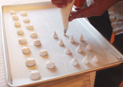 "Meringue  ""puffs"" are placed on a half sheet pan before baking to make the decorative mushrooms."