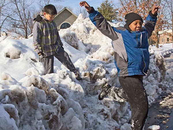 Another round of snow is making its way through the Philadelphia area early this morning, with most of the region seeing only a few inches. Here, Yunny Jeong, 9 and (right) Justine Jones, 11, both of Montgomeryville, navigate over a pile on plowed snow on Hunt Club Trail, Montgomeryville, February 17, 2014.  ( DAVID M WARREN / Staff Photographer )