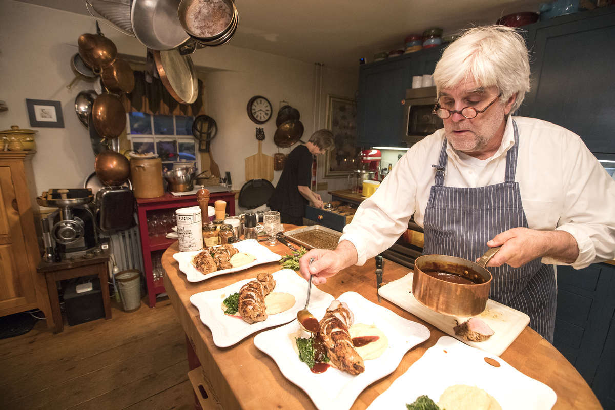 Martin Gagne plates the pork tenderloin. Each table receives a platter family style. (CHARLES FOX / Staff Photographer)