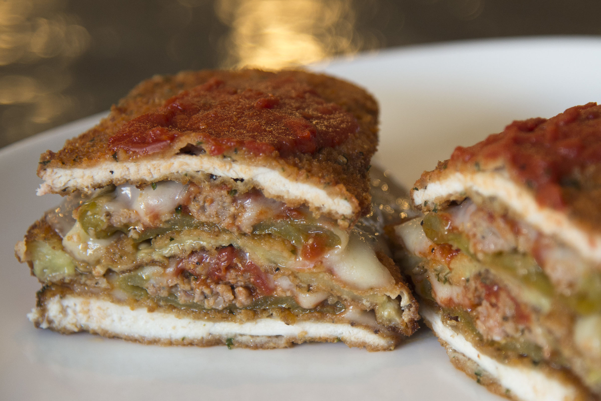 "The ""Cutlet Stack, "" a stack of chicken cutlets, eggplant cutlet and sausage-stuffed long hots cooked Parmesan style at Cotoletta, in Bala Cynwyd. (TOM GRALISH / Staff Photographer)"