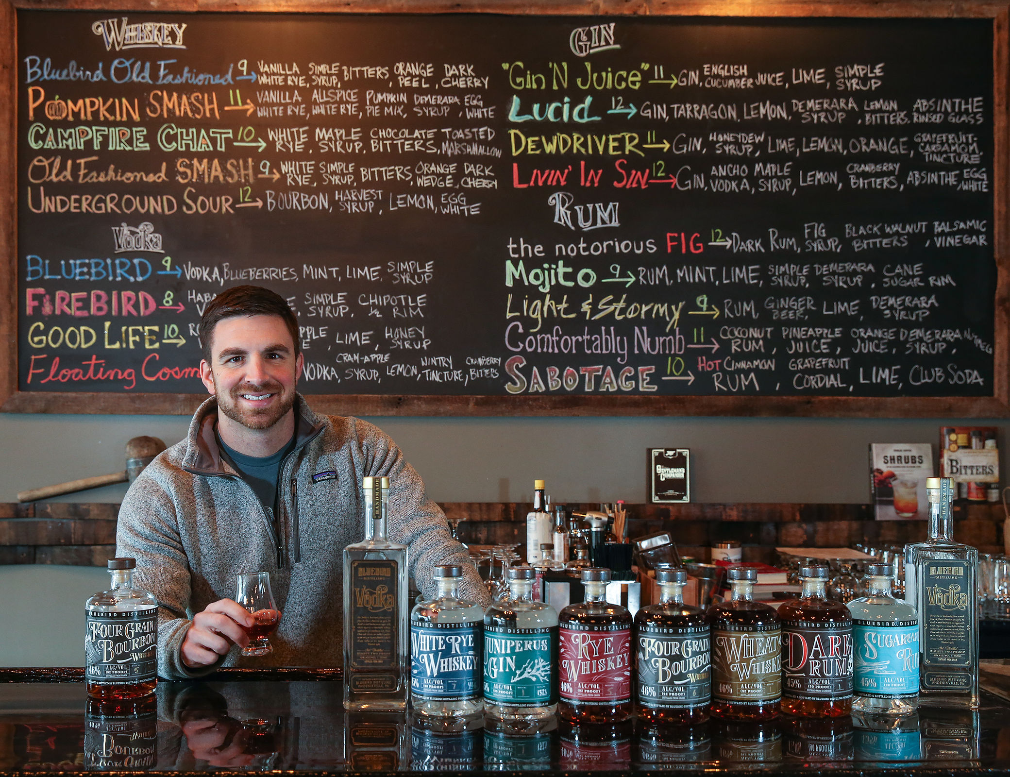 With his wares, Jared Adkins, owner of Bluebird Distilling, Phoenixville. (STEVEN M. FALK / Staff Photographer)