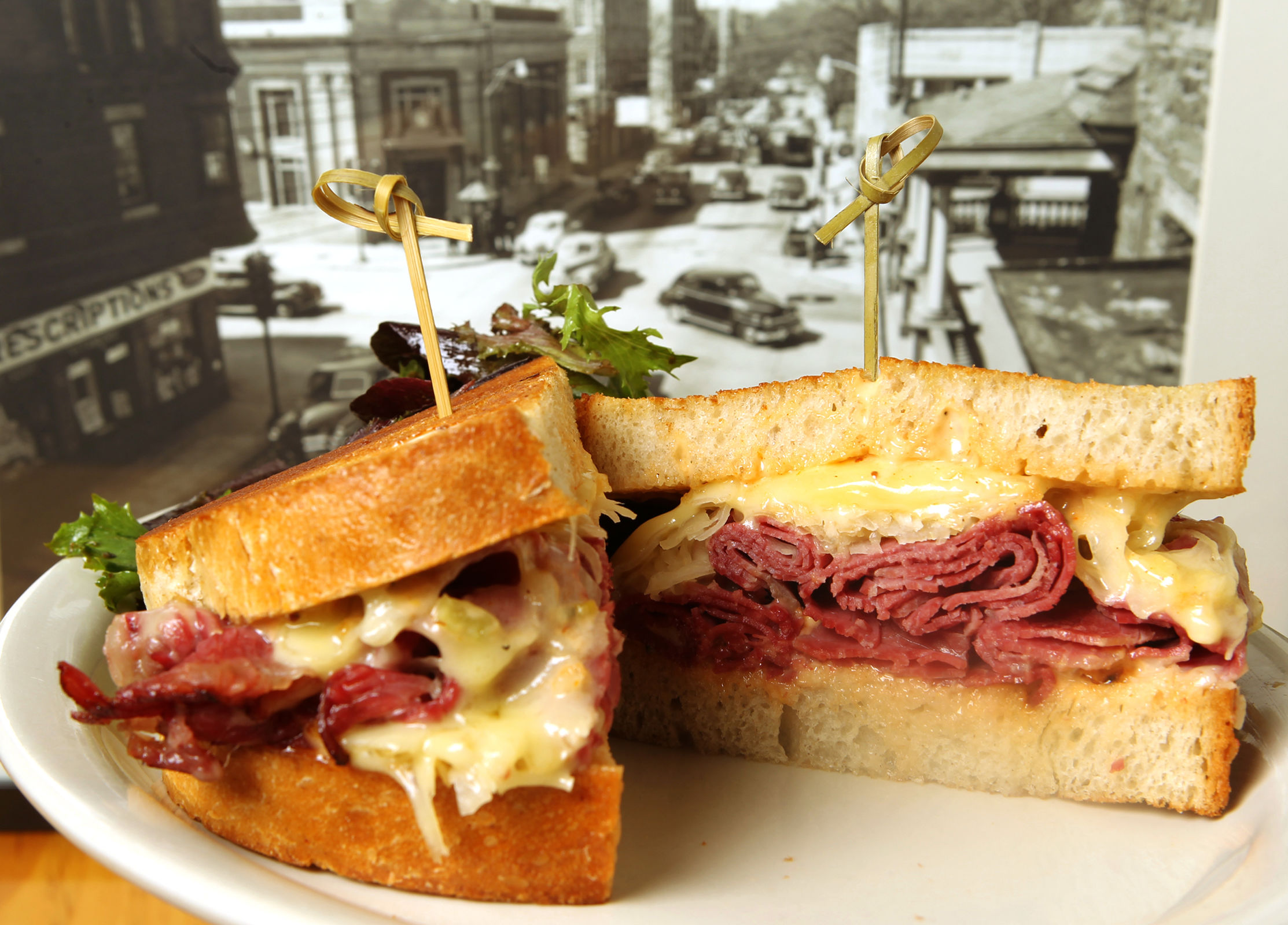 The House Cured Corned Beef Reuben from The Avenue Delicatessen shown on one of the historic Lansdowne photos that decorate the interior. (CHARLES FOX / Staff Photographer)