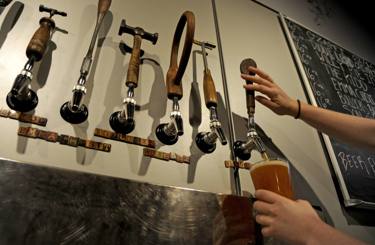 Antique farm tools top the taps at Kennett Brewing Co. (TOM GRALISH / Staff Photographer)