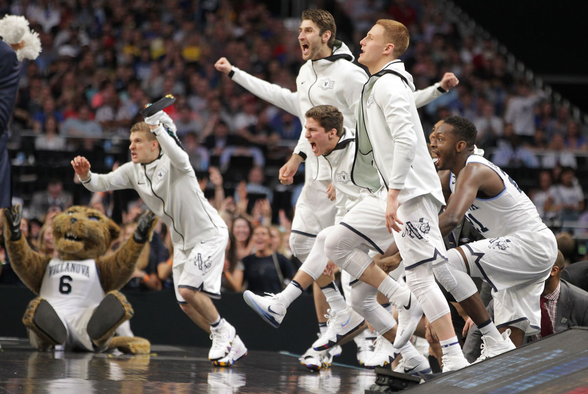 The Villanova bench leaps onto the court after an early run forced Kansas to call timeout during the national semifinals at the Alamodome.  (CHARLES FOX / Staff Photographer)