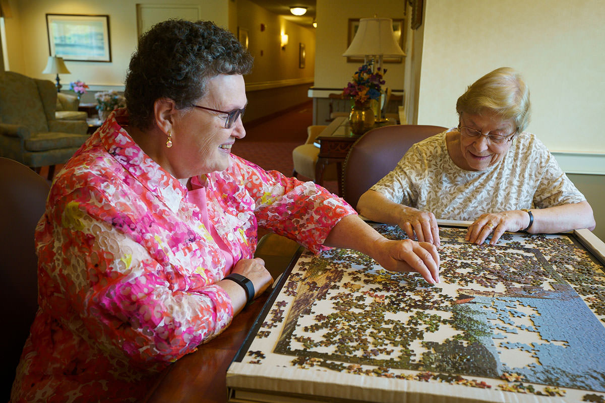Caroline Wroblewski, 75, left, puts together a puzzle with her friend Patricia Angelucci, right, 89, at Normandy Farms Estates retirement community, in Blue Bell. (JESSICA GRIFFIN / Staff Photographer)