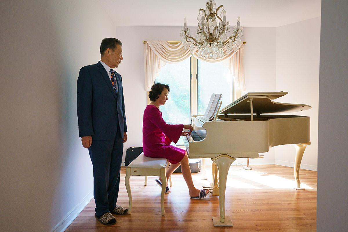 Young Bin Lee, a neuropsychiatrist, stays young by trying to think like a younger person. He is shown here listening as his wife Euli plays piano in their Medford home. (JESSICA GRIFFIN / Staff Photographer)