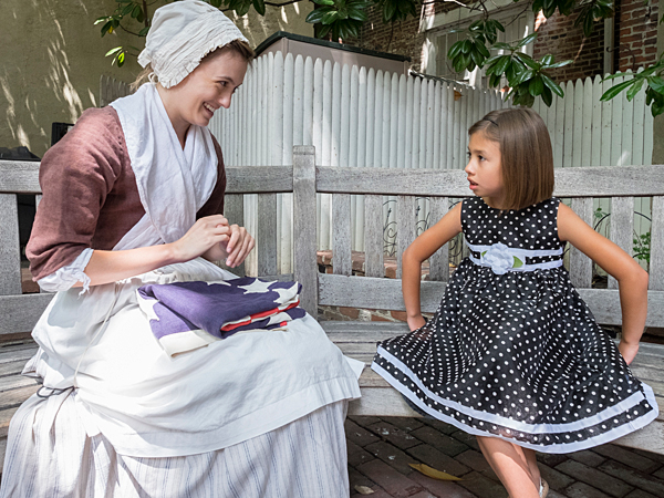 """On the story telling bench at the Betsy Ross house, Joanna Harris and """"history maker"""" Meredith LaBoon who portrays Betsy Ross, exchange stories. ( ED HILLE / Staff Photographer )"""