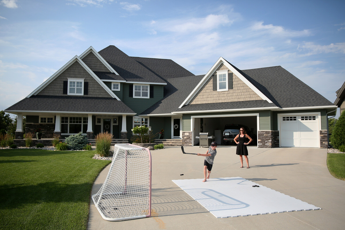 Erinn O'Keefe Hakstol watches her son Brenden, 10, show off his hockey skills in front of their Grand Forks home. (TIM TAI / Staff Photographer)